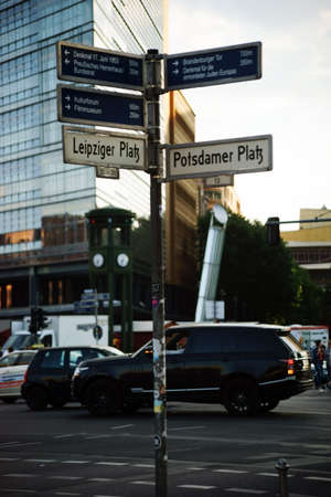 distances: Berlin, Germany - May 10, 2016: Road traffic passing a way sign at the Leipzig and Potsdam Square with distances to various attractions on May 10, 2016 in Berlin.