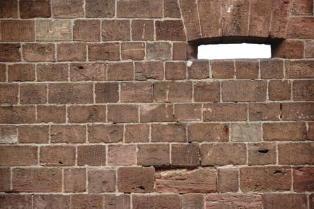 demarcation: A wall of striking wine-red stones with a loophole or a window.