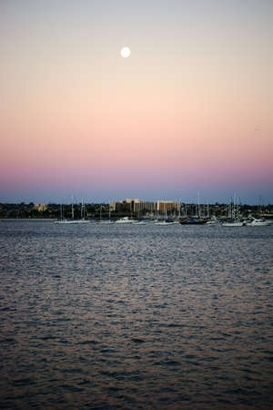 colorful sunrise: Colorful sunrise in the morning in the San Diego Bay under the full moon. Stock Photo