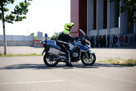 Mainz, Germany - August 6, 2016: A policeman on a motorcycle watches fans at the entrance of the Opel Arena at a soccer game of 1. FSV Mainz 05 on August 6, 2016 in Mainz. Editorial