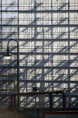 inserts: The Pipes and wooden inserts from a scaffolding cast abstract shadows on a plastic sheet.