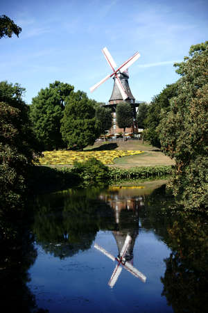 flower beds: The Windmill Am Wall or mill on the wall with flower beds behind a pond.