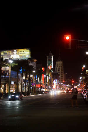 semaforo peatonal: Los Angeles, United States - December 27, 2015: A pedestrian crosses a traffic light at the night lit Hollywood Boulevard with traffic on December 27, 2015 in Los Angeles.