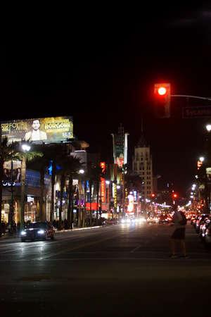 semaforo peatonal: Los Ángeles, Estados Unidos - 27 de diciembre de 2015: Un peatón cruza un semáforo en la noche iluminada Hollywood Boulevard con el tráfico el 27 de diciembre de 2015, de Los Ángeles. Editorial