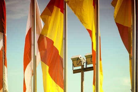 floodlights: The Spanish and Polish flags against a blue sky with two floodlights.