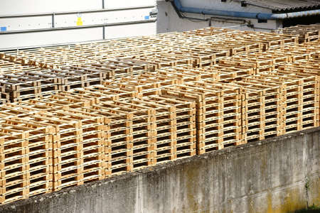demarcation: Stacked wooden pallets are in the backyard of a factory.