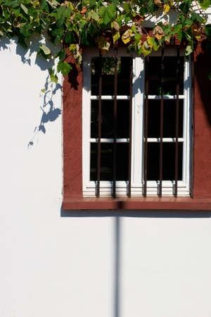 rejas de hierro: Las ventanas de madera nostálgicas de un edificio catalogado con barras de hierro antes de la trama, una fachada brillante y hojas de parra.
