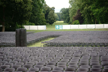salida emergencia: Parallel arranged empty seat rows of folding chairs on a lawn of an open-air concert with an emergency exit. Foto de archivo