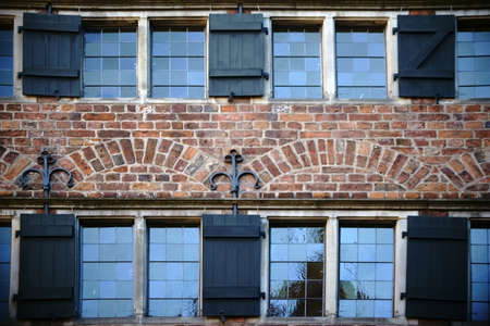 ironwork: A brick building with open nostalgic shutters and ironwork.