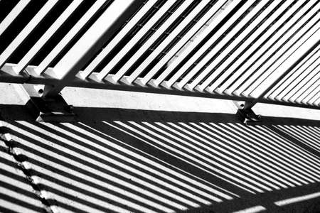 crossbars: The metal railing of a bridge railing casts a shadow. Stock Photo