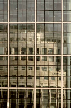 London, UK - November 29, 2014: The reflection of the Thomson Reuters office building in the modern mirror facade of another office building on November 29, 2014 in London.