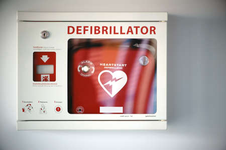 A survival box with a defibrillator on a wall of an public building.