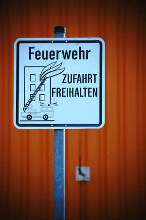 fire brigade: A sign for a fire brigade entrance in front of an abstract orange facade. Stock Photo