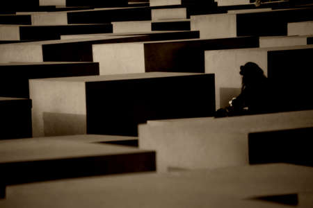 concrete blocks: Berlin, Germany - May 10, 2016: A tourist stands between the gray concrete blocks of the Monument to the Murdered Jews of Europe on May 10, 2016 in Berlin. Editorial
