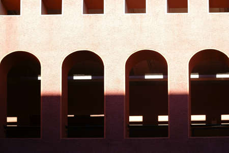 open windows: An open passage with arched windows outside a public building. Stock Photo