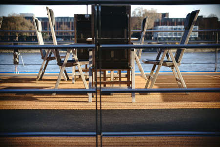 passenger ship: The classy sun deck a passenger ship with a glass reiling, carpets, tables and chairs.