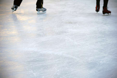 skaters: The close-up of the skates from ice skaters on an ice surface.                          Stock Photo