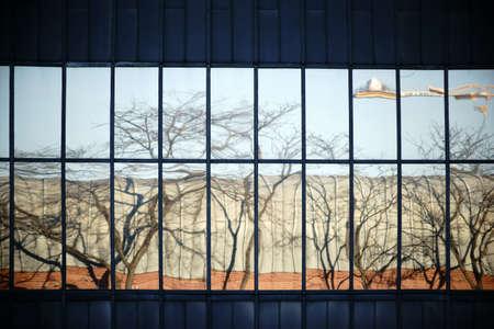 Die abstrakte Spiegelung einer Hausfassade mit Fenstern in einer anderen Hausfassade mit Fenstern.