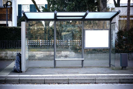 The glass shelter of a bus stop on a street.