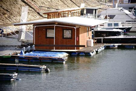 A small wooden houseboat as well as yachts and motor boats anchored in an inland port on the River Rhine.