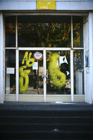 shut down: A descended building with a smeared entrance door and a yellow facade.