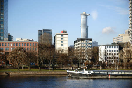 Office buildings, business buildings and residential buildings behind the river Main in Frankfurt, on Which a ship travels. Stock Photo