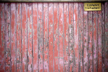 A heavily worn wooden gate with a yellow sign: keep exit.