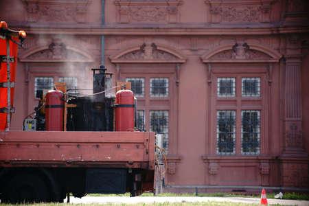 Een voertuig met een verwarmde trolley voor het repareren van wegschade. Stockfoto