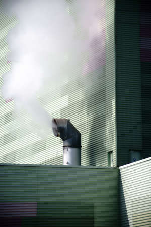 The smoky chimney of an industrial plant on the outside wall of a power plant.                             Фото со стока