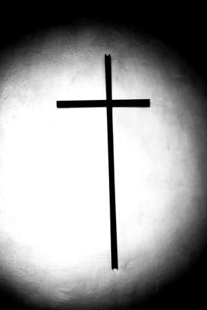 In a dark crypt, a beam of light passes directly into the center of a cross.