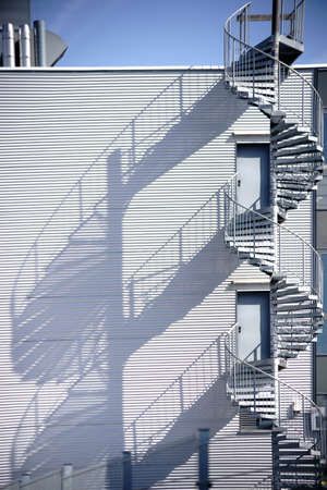 rungs: A spiral staircase, fire escape on the side of a industrial building facade.