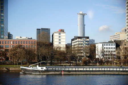 Office buildings, business buildings and residential buildings behind the river Main in Frankfurt, on Which a ship travels. Editorial