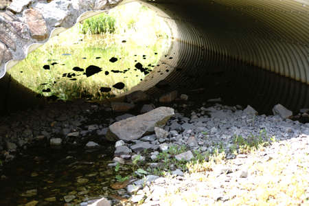The top view and close-up on the stones of a rubbish bed of a pond under a tubular bridge underpass.