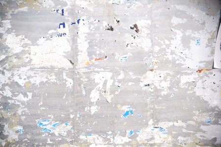The close-up of a billboard with torn paper shreds of posters and advertising posters.                               Stock Photo