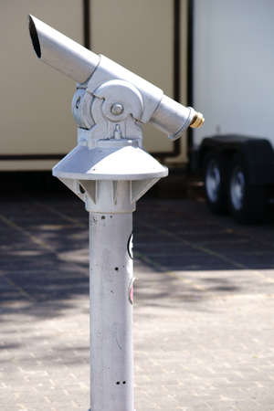 A coin telescope mounted on a pillar for landscape observation.