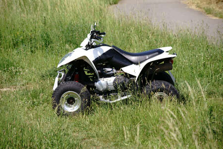 A quad terrain vehicle standing on a meadow in the field.                       Stock Photo