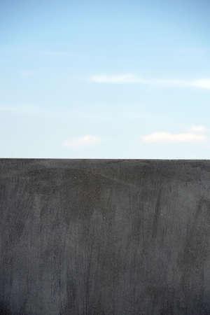 A homogeneous and modern gray wall edge against a blue sky. Reklamní fotografie