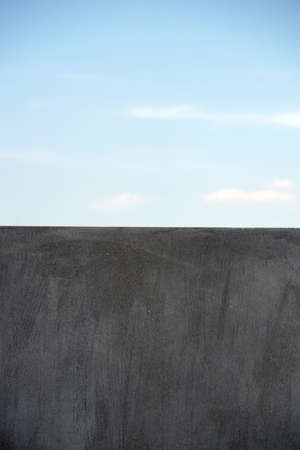 edgy: A homogeneous and modern gray wall edge against a blue sky. Stock Photo