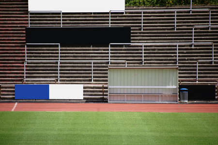 Seating of a grandstand behind a coach bench in a soccer stadium.           Stock Photo