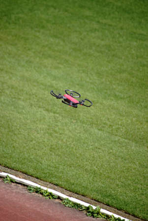 A quadrocopter, a rotors-driven aircraft flying over a lawn.                        Stock Photo