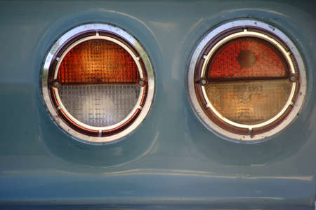 The closeup of a round taillight from a vintage car.