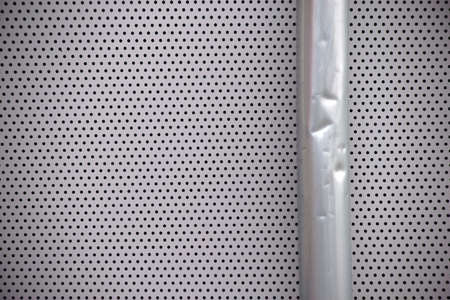 The cutout and the close-up of a battered drainpipe at a perforated plate. Stock Photo