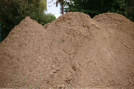 A construction site with worn out earth piled up to a sand pile.