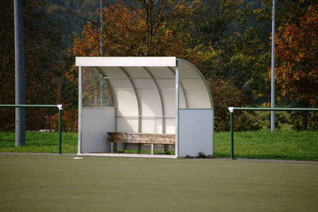 A coach bench stands on the edge of a soccer field in a soccer stadium.