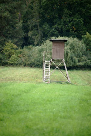 A high seat and hunting camp stands on the edge of a forest on a field.