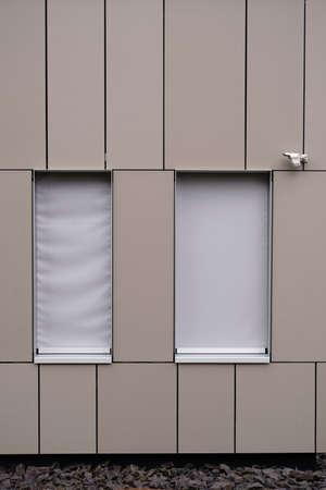 A modern house facade with sheet metal covering and an installed surveillance camera. Reklamní fotografie - 87998220