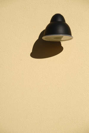 graining: The close up of a wall lamp casting a shadow at a plaster facade.