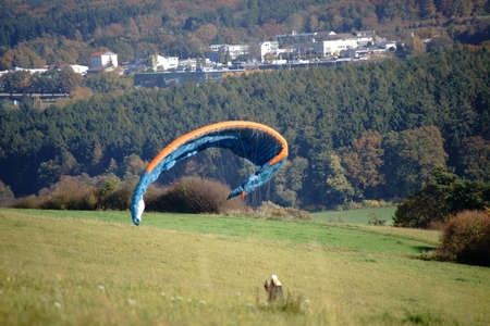 A paraglider is standing on a hill and straightens its paraglider.