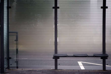A mist-fogged windowpane of a newly built glass shelter of a tram stop.