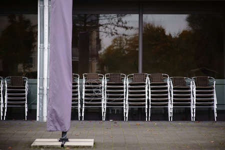 The granted and stacked outdoor chairs of a caf� and restaurant.